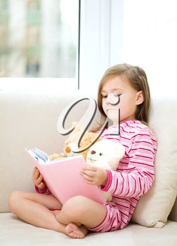 Little girl is reading a story for her teddy bears while laying in bed and wearing pajama, indoor shoot