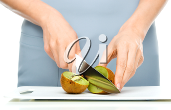 Cook is chopping kiwi fruit, closeup shoot, isolated over white