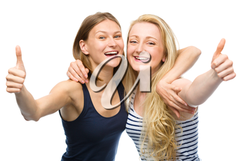 Two young happy women are hugging and showing thumb up sign, isolated over white