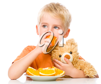 Portrait of a little boy with his teddy bear and oranges, isolated over white