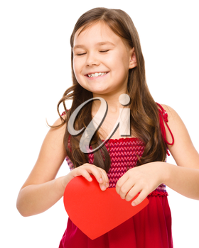 Portrait of a sad little girl tearing red heart apart, isolated over white