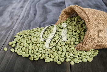 burlap sack of green coffee beans on old wooden table