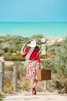 Nice Woman traveler in retro style dress walking through dunes to the beach