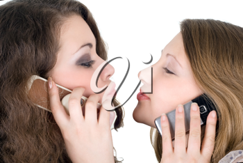 Royalty Free Photo of Two Girls on Cellphones Appearing Ready to Kiss