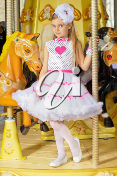 Little beautiful girl in pink and white dress standing on the carousel