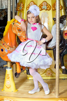 Little beautiful girl in pink and white dress leaning on a carousel pony