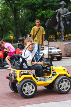 NIKOLAEV, UKRAINE - June 21, 2014: Kids in the play area riding a toy car