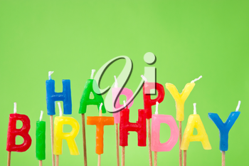 colorful candles forming the sentence happy birthday on green background