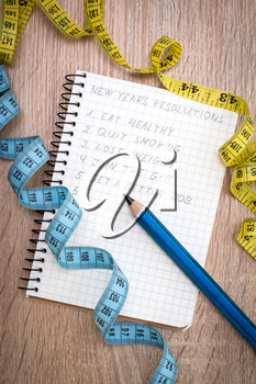 Measure tape and  notepad with New Year's resolutions