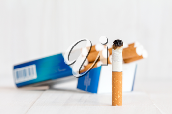 Cigarette package and butt on white wooden background