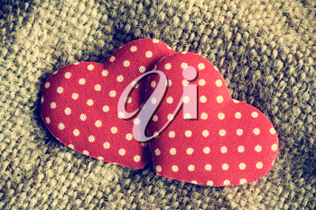 Two red decorative hearts on sackcloth background.Vintage style.