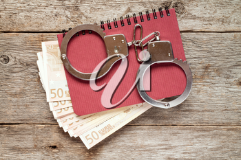 Handcuffs on notebook with euro banknotes. Bribery concept.