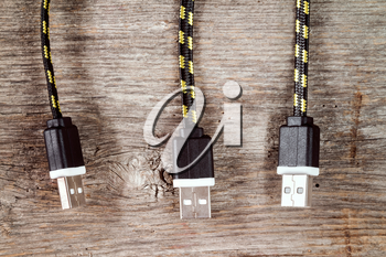 Three USB cables hanging over wooden background