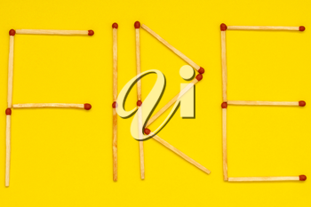 Word FIRE made with matches on yellow background