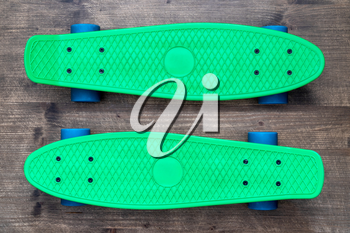 Two green skateboards on wooden background, top view