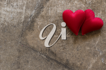 Two cute red hearts on the old grunge background. Copy space.