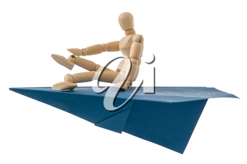 Wooden doll flying on a blue paper plane. Isolated on white background.