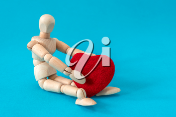 Wooden man sitting and holding red heart. Copy space.