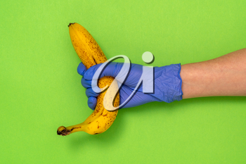 Hand in a latex glove holding a banana on green background with copy space. Grocery stores during COVID-19 lockdown.