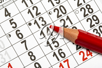 Monthly calendar and a red pencil to mark the desired date
