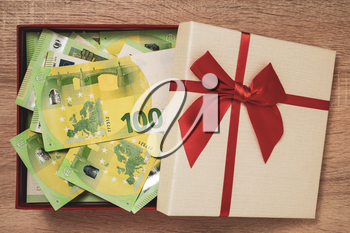 Open gift box full of money. Euro currency in the gift box with red ribbon.