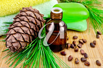 Cedar oil in a bottle, with a branch of cedar cones, cedar nuts, two green soap, two towels on a bamboo mat