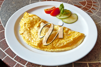 Yellow omelet, two slices of red tomatoes and cucumber, a sprig of parsley on the plate against the backdrop of granite countertops with a pattern