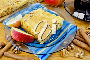 Apple pie, walnuts, cinnamon sticks, apple, tea in a glass cup, a blue cloth on the background of wooden boards