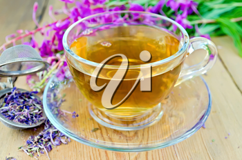 Herbal tea in a glass cup, metal sieve with dry flowers fireweed, fireweed fresh flowers on a wooden board