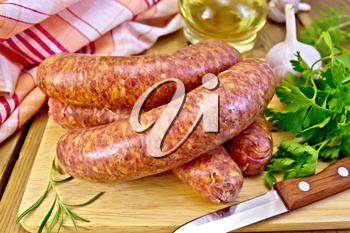 Raw beef sausages, knife, rosemary, parsley, vegetable oil, napkin on a wooden boards background