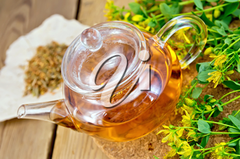 Tea in a glass teapot on stand, fresh and dried flowers of Hypericum on a wooden boards background