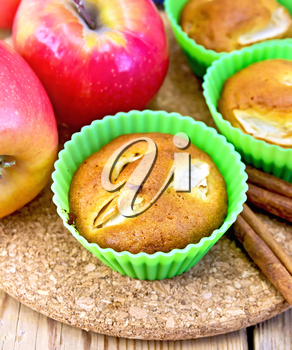 Cupcake wheat with apples in silicone molds, cinnamon, napkin on a wooden boards background