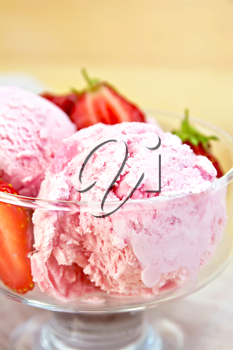 Strawberry ice cream in a glass bowl with strawberries on a napkin on a wooden boards background