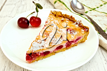 Pie with cherries and sour cream in a dish, towel with a spoon on a background of wooden boards