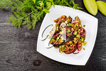 Salad of fried eggplant, fresh and pickled cucumber with red onion, seasoned with vegetable oil and spicy sauce in a plate, towel, fork and dill on a black wooden board background from above