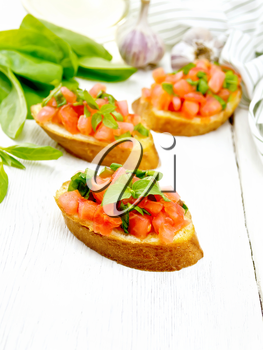 Bruschetta with tomato, basil and spinach, fresh spinach leaves, towel, garlic and vegetable oil in a carafe on the background of light wooden board