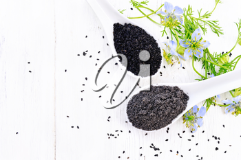 Flour and seeds of Nigella sativa in two spoons, sprigs of kalingini with blue flowers and green leaves on a wooden board background from above