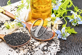Flour and seeds of Nigella sativa in two spoons on a burlap, oil in the bottle and twigs of kalingini with blue flowers and green leaves on wooden board background