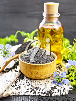 Flour of black caraway in a bowl, seeds in a spoon burlap, oil in bottle and twigs Nigella sativa with blue flowers and leaves on wooden board background