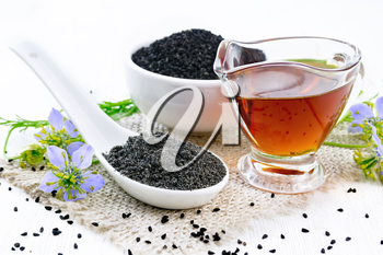 Flour Nigella sativa in a spoon, black cumin seeds in a bowl and oil in gravy boat on burlap, sprigs of kalingi with blue flowers and leaves on wooden board background