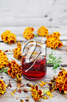 Alcohol tincture of marigolds in a glass jar, fresh and dried flowers on wooden board background