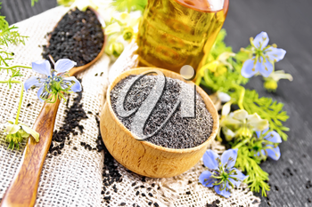 Flour of black caraway in a bowl, seeds in a spoon burlap, oil in bottle and twigs Nigella sativa with blue flowers and green leaves on dark wooden board background