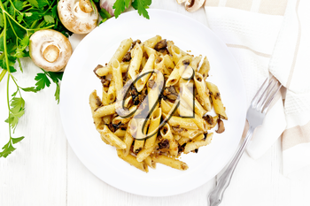Penne pasta with wild mushrooms in a plate, towel, parsley and fork on a wooden board background from above