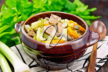 Eintopf soup made from pork, celery, beans, carrots and potatoes with leek in a clay bowl on a napkin on wooden board background