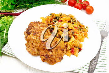 Fritters of minced meat with stewed cabbage in a plate, fork on towel, tomatoes, parsley and chard on light wooden board background