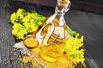 Mustard oil in a glass jar and decanter, mustard grains on a burlap napkin, flowers and leaves on black wooden board background