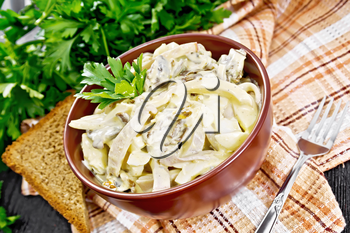 Salad with squid, egg and champignons in a bowl on a towel, bread, fork and parsley on wooden board background
