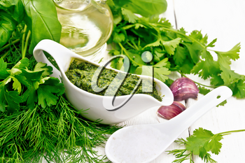Sauce of dill, parsley, basil, cilantro, other spicy herbs, garlic and vegetable oil in a gravy boat, a spoon with coarse salt on wooden board background