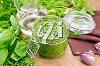 Sauce of dill, parsley, basil, cilantro, other spicy herbs, garlic and vegetable oil in a glass jar, a towel on wooden board background