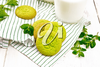 Green mint cookies on a towel with milk in a glass on wooden board background